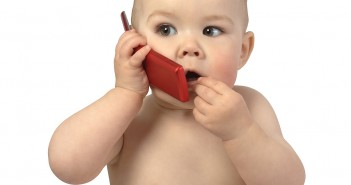 Cute child talking to a cell phone, isolated over white